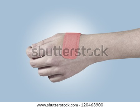 Adhesive Healing plaster on hand. Concept photo with Color Enhanced skin with read spot indicating location of the wound. - stock photo