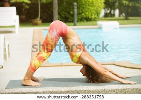 "Adho Mukha shvanasana.girl doing asana ""dog muzzle down"" by the pool - stock photo"