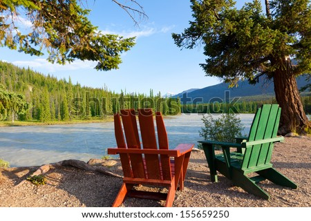adirondack chairs by the beautiful river in jasper national park, alberta, canada - stock photo