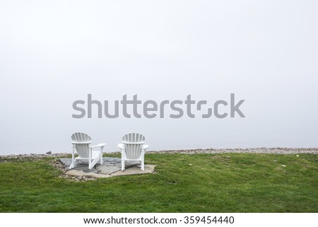 Adirondack Chairs on a cloudy day at the lakeside.  Muskoka Chairs - stock photo