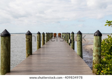 Adirondack chairs on a wooden pier in the tropics - stock photo