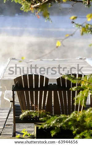 Adirondack Chairs on dock look out onto misty autumn lake water/Misty Autumn Morning/The Beauty of Autumn - stock photo