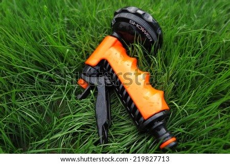 Adjustable shower (spray) lying on the fresh lawn grass in the summer garden