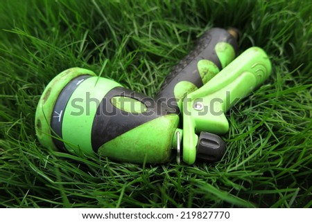 Adjustable shower (spray) lying on the fresh lawn grass in the summer garden - stock photo