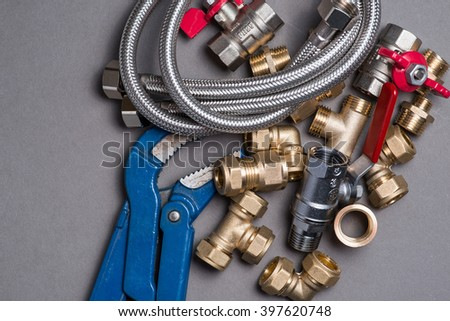 Adjustable spanner with assorted plumbing fittings and hose on grey surface