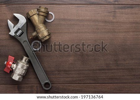 adjustable wrench and pipes on the wooden background - stock photo