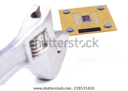 Adjustable wrench holding PC CPU. Closeup with shallow DOF. Isolated on white background. - stock photo