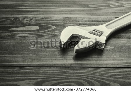 Adjustable wrench on black wooden background - stock photo