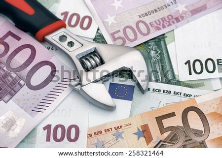 Adjustable wrench on euro banknotes. Conceptual image.