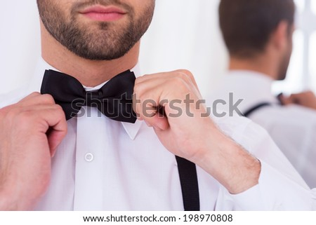 Adjusting his bow tie. Close-up of young man in white shirt adjusting his bow tie while standing against mirror - stock photo