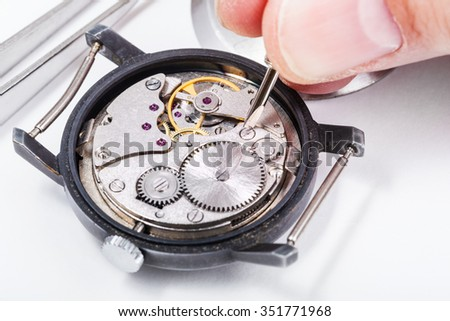 adjusting old mechanic wristwatch - horologist repairs old watch close up - stock photo