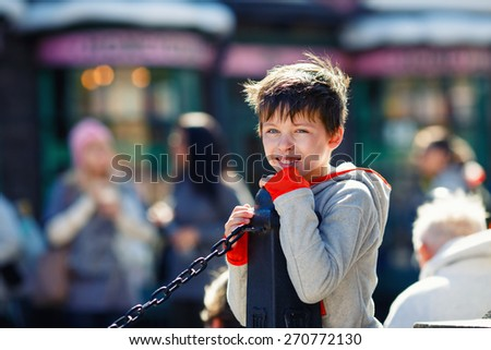 Admiring little boy laughing outdoors in town on summer day - stock photo