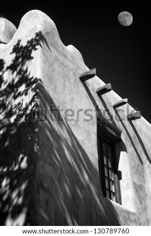 Adobe building in downtown Santa Fe, New Mexico, USA with the moon in the background sky - stock photo