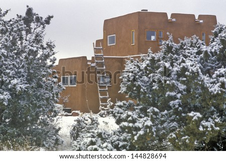 Adobe in snow in Santa Fe, NM - stock photo