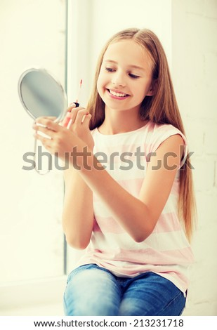 adolescence, beauty, makeup, happy people concept - teenage girl with lip gloss and mirror - stock photo
