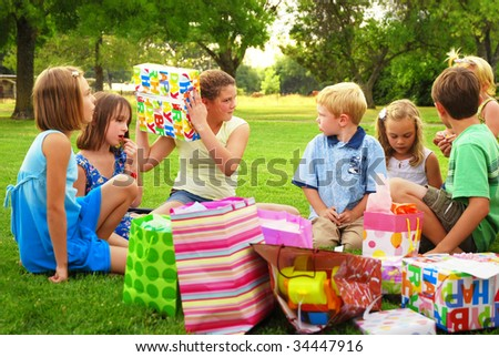 Adolescent girl shakes a gift during her birthday party - stock photo