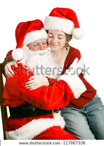 Adolescent girl sitting on Santa Claus' Lap, getting a hug.  We're never too old for Christmas!  White background. - stock photo