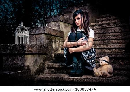 Adolescent lolita schoolgirl sitting on stairs looking sad - stock photo
