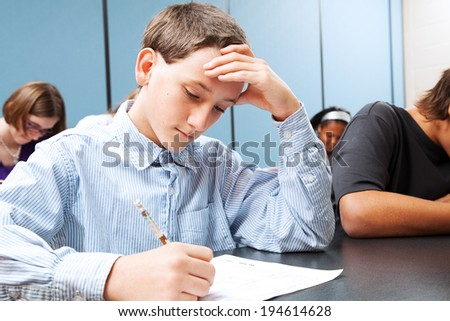 Adolescent middle school boy concentrats on a standardized test in school.   - stock photo