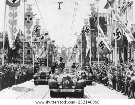 Adolf Hitler waving to crowds from his car at the head of a parade. The streets are decorated with various swastika banners. Ca. 1934-38. Location is unidentified. - stock photo