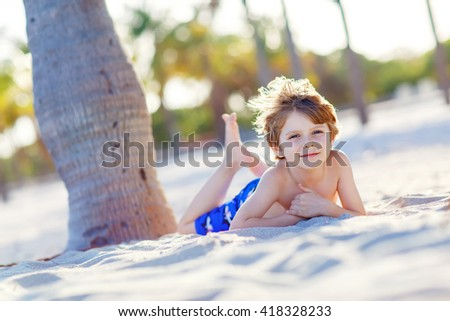 Adorable active little kid boy having fun on Miami beach, Key Biscayne. Happy cute child relaxing and enjoying sunny warm day near palms.