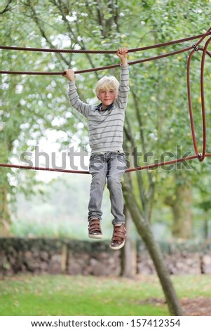 Adorable active teenager boy climbs on the ropes at playground in the park - stock photo