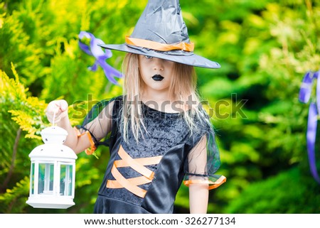 Adorable amasing little girl wearing witch costume on Halloween outdoors. Trick or treat. - stock photo