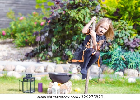 Adorable amasing little girl wearing witch costume on Halloween. Trick or treat. - stock photo
