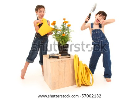 Adorable 6 and 7 year old french american kids being goofy with potted marigold plant over white background. - stock photo