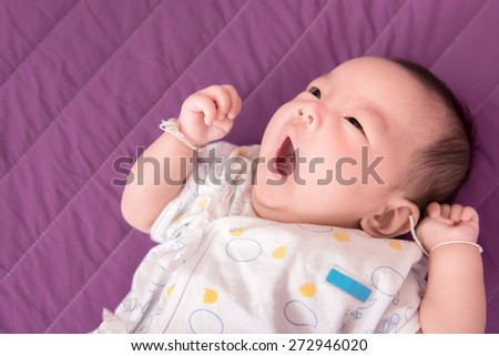 Adorable asian baby girl on the bed - stock photo