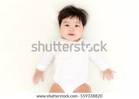 Adorable asian baby girl smiling on the bed.