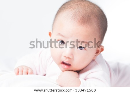 Adorable Asian baby 4-5 months old on white bed & background. Portrait studio light isolated.