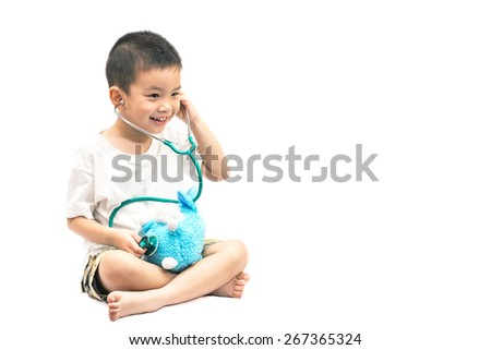 Adorable asian child playing as doctor with bear isolated on white background - stock photo