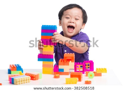 Adorable asian child playing colorful toys isolated - stock photo