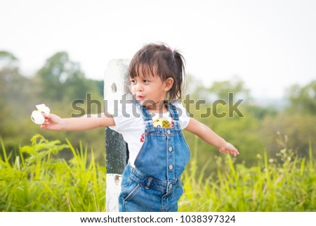 Adorable asian little girl acting like flying and she holding the flower on the right hand, concept of happy and healthy kid lifestyle.