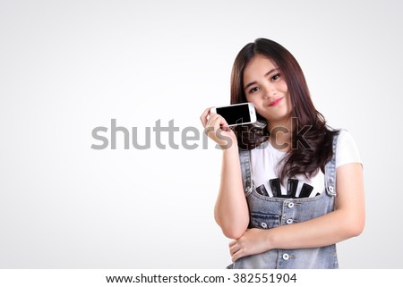 Adorable Asian teenage girl holding her smartphone in cute pose, over white background for copy space - stock photo