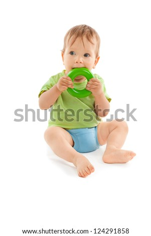 Adorable baby biting a toy and sitting on the floor isolated on white