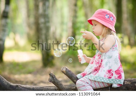 Adorable baby blow soap bubbles in park - stock photo