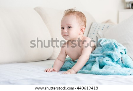 Adorable baby boy after shower covered in blue blanket on sofa at living room - stock photo