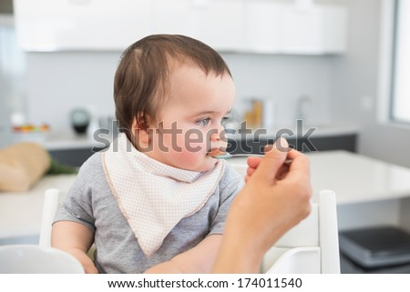 Adorable baby boy being fed by mother in kitchen - stock photo