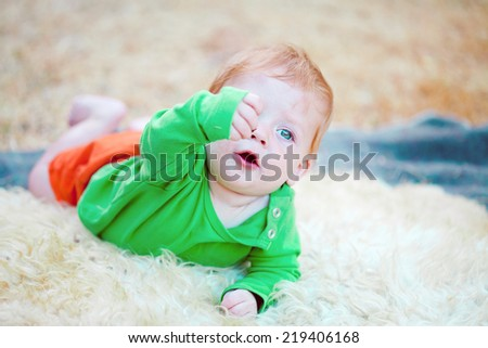 Adorable baby boy crawling on the blanket while holding up something he found - stock photo