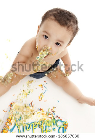 Adorable baby boy eating a birthday cake.  Isolated on white. - stock photo
