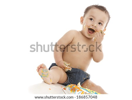 Adorable baby boy eating a birthday cake.  Isolated on white with room for your text.   - stock photo