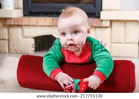 Adorable baby boy in santa clothes with christmas decoration - stock photo