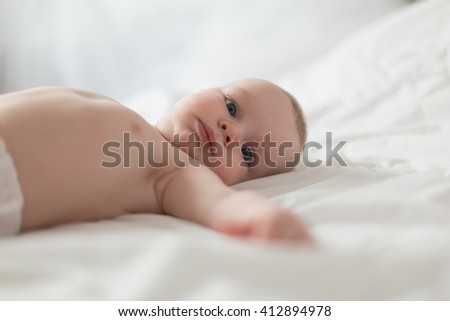 Adorable baby boy in white sunny bedroom.