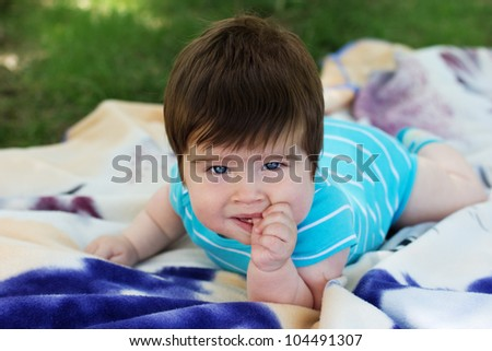 Adorable baby boy laying on grass in spring flowery garden.