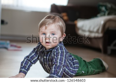 Adorable baby boy learning crawling indoor