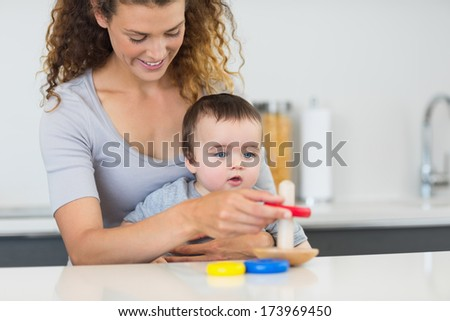 Adorable baby boy looking at mother playing with toys in kitchen - stock photo
