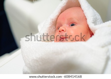 Adorable baby boy looking out under white towel