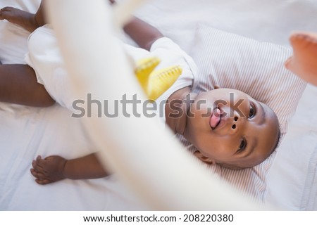 Adorable baby boy lying in his crib playing with mobile at home in the bedroom - stock photo
